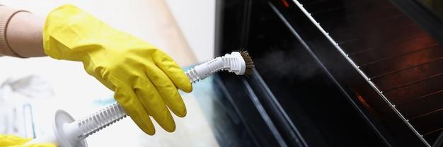 Женские руки в желтых перчатках держат пароочиститель и чистят пароочиститель духовки для