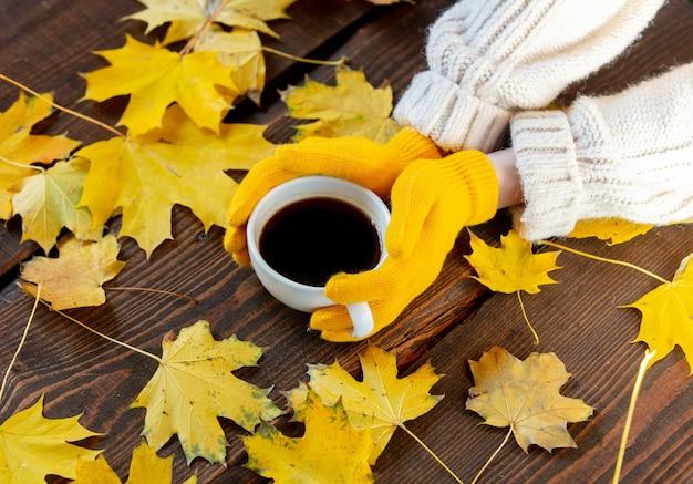 Женские руки в желтых перчатках держат чашку кофе рядом с кленовыми листьями на деревянном столе