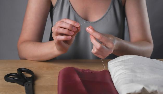 Женские руки заправляют нить через крошечное игольное отверстие для шитья