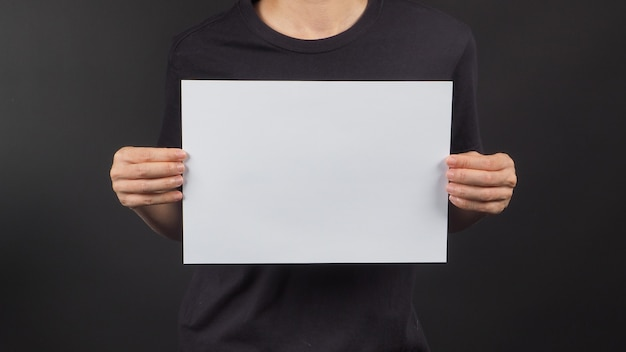 Женские руки держат чистый лист a4 на черном фоне.
