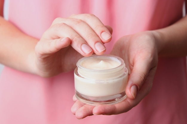 Female hands and jar of cream closeup with place to text
