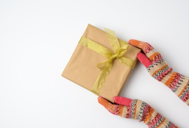 Female hands in knitted mittens hold a square box wrapped in brown paper and tied with a golden ribbon on white, top view