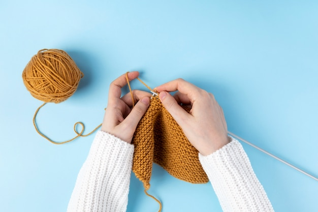 Female hands knitting with yellow wool, blue background. top view