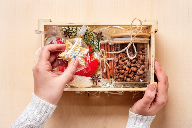 Female hands laid care package, seasonal gift box with coffee, gingerbread and cinnamon
