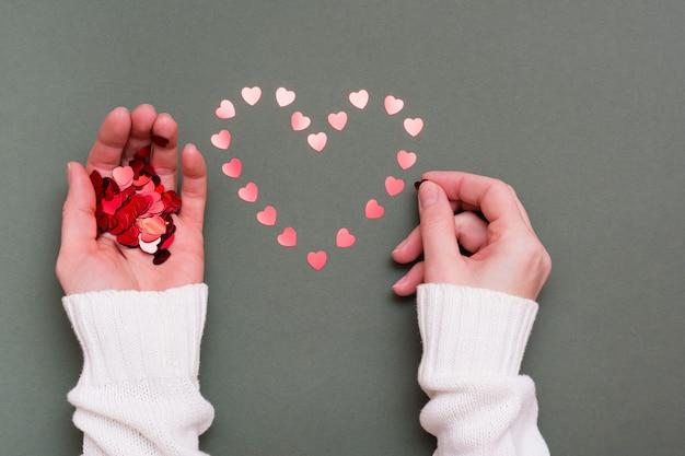 여성의 손은 작은 마음에서 녹색 배경에 심장 모양 배치