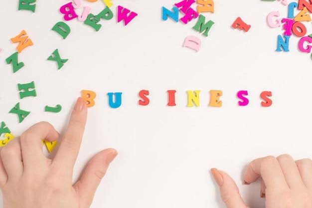 女性の手は、マルチカラーの文字からビジネスという言葉をレイアウトします