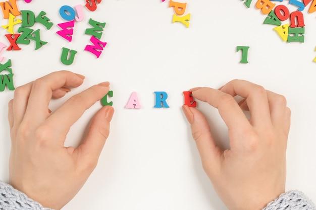 女性の手は色付きの文字から単語ケアをレイアウトします