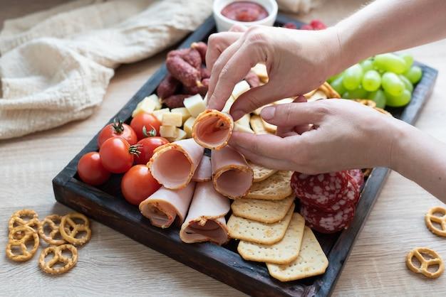 ソーセージ、フルーツ、チーズ、パーティー料理と一緒に豚肉のボードにハムを置く女性の手。