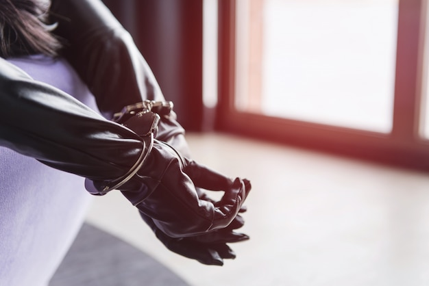Female hands in leather gloves and handcuffs close-up