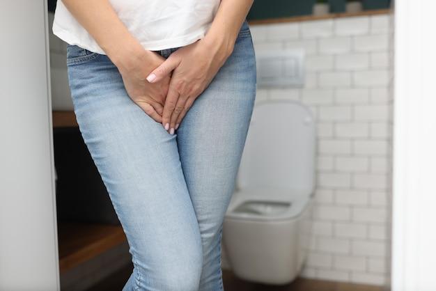 Female hands between legs in jeans