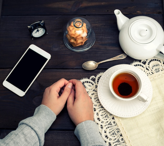 Female hands lie on a wooden table, next to a cup of tea and a smartphone
