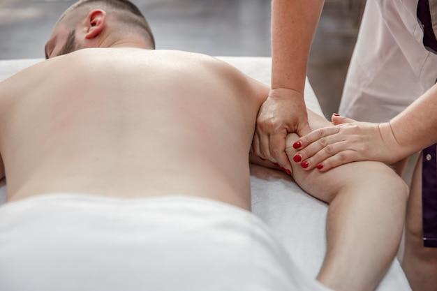 여성의 손은 살롱에 있는 남자에게 몸의 치료 마사지를 합니다.