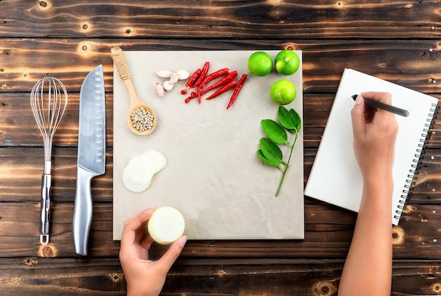 女性の手は材料を使って木製テーブルのダイエットブックでメモを作り、