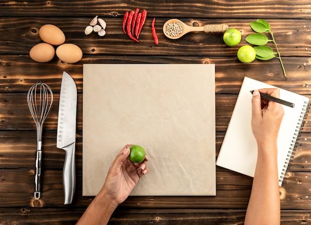 女性の手は材料を使って木製テーブルのダイエットブックでメモを取る