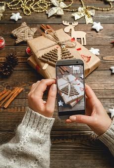 女性の手がクリスマスアクセサリーの写真を作る