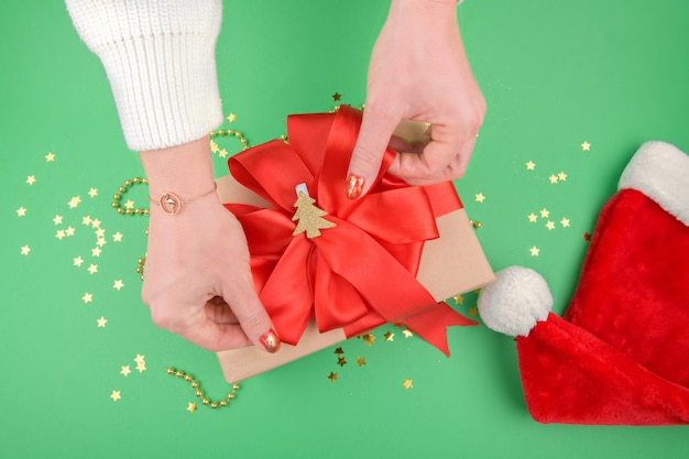 Female hands making a christmas gift with red bow on green background