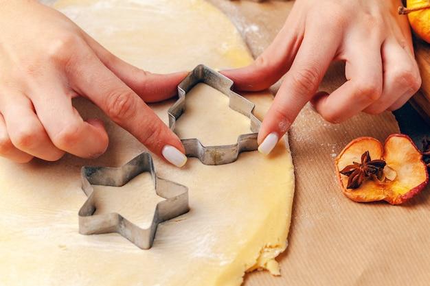 家で新鮮な生地からクッキーを作る女性の手
