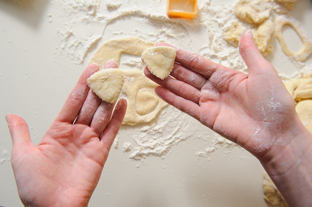 Female hands making cookies from fresh dough