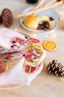 Женские руки делают бутерброд с салями вяленой колбасы