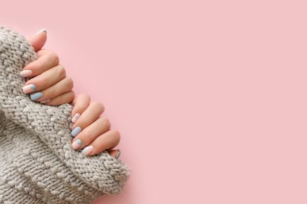 여성 손 매니큐어 니트 스웨터와보기를 닫습니다. 유행 기하학적 네일 아트 매니큐어. 매니큐어 살롱 배너 개념
