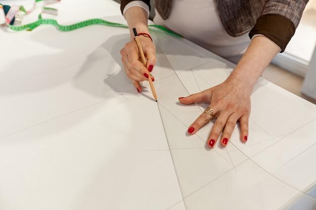 Женские руки, размечающие узор на белом столе
