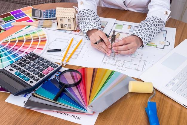 オフィスで家の計画を測定する女性の手