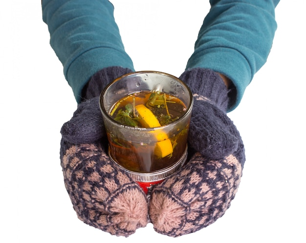 Female hands in mittens, holding an old glass with tea.