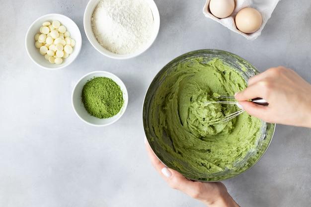 テーブルの上で生地と泡立て器とレシピの材料を混ぜる女性の手