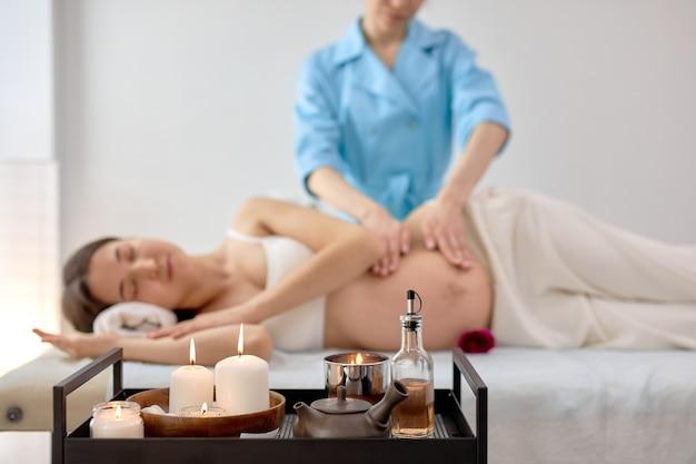 마사지 치료사의 여성 손은 미용실, 스파 또는 실내 웰빙 센터에서 임신한 여성의 배를 가볍게 마사지합니다. 측면보기. 테이블에 촛불에 초점