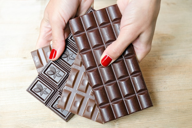 Female hands offer chocolate bars