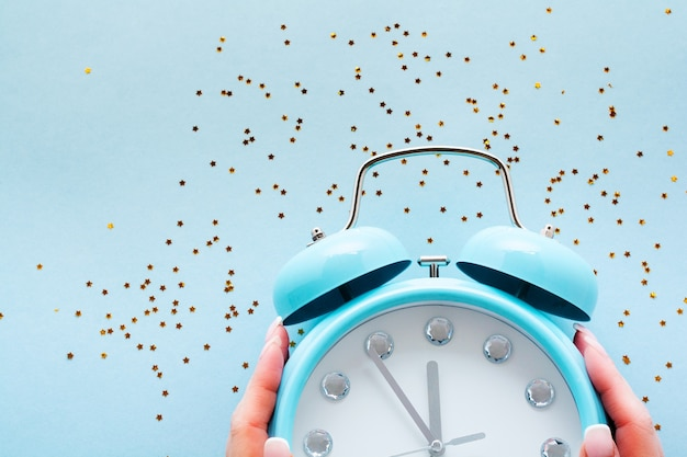 23時間55分を示す大きな青い目覚まし時計の女性の手。水色の表面に光沢のある星があります。上面図。