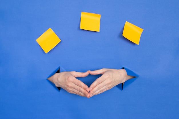 Женские руки на синем фоне, жест уверенности. женские вставлены в бумажный фон, сверху три бумажные палочки. место для надписи.