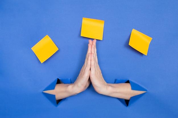 Женские руки на синем фоне, жест благодарности. женские вставлены в бумажный фон, сверху три бумажные палочки. место для надписи.