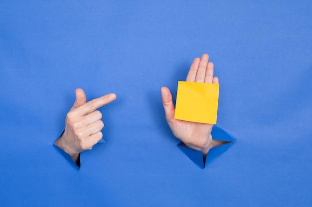 Женские руки на синем фоне, показывая указательный палец на наклейке. женские вставлены в бумажный фон, сверху три бумажные палочки. место для надписи.