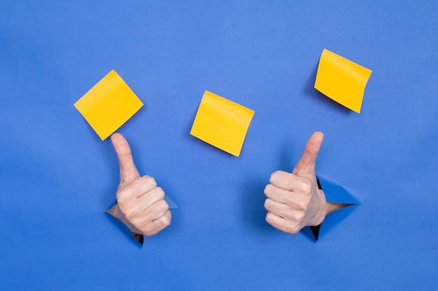 Женские руки на синем фоне, пальцы вверх. женские вставлены в бумажный фон, сверху три бумажные палочки. место для надписи.