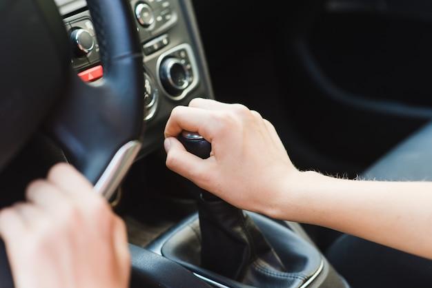 Женские руки на рычаге переключения передач
