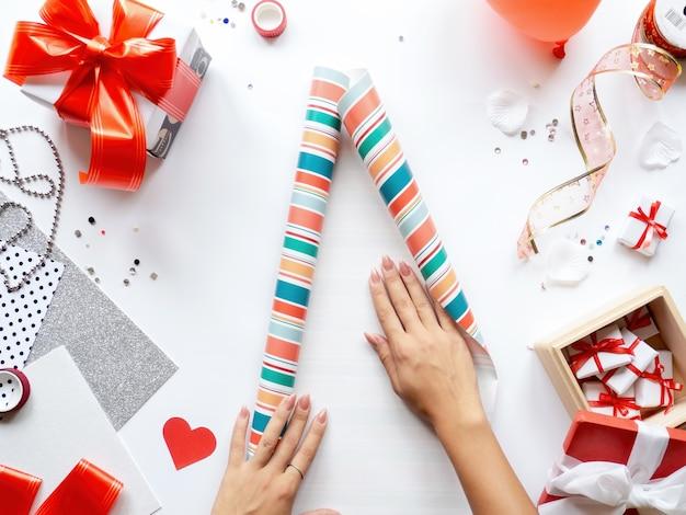 Женские руки на столе с вещами для подготовки подарков