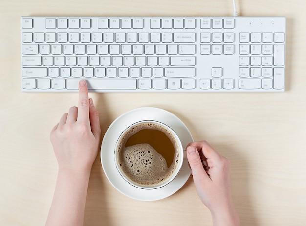 キーボードの女性の手とコーヒーのカップを保持します。