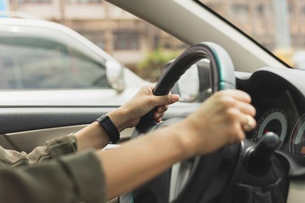 道路を運転中の女性が車のステアリングホイールに手します。