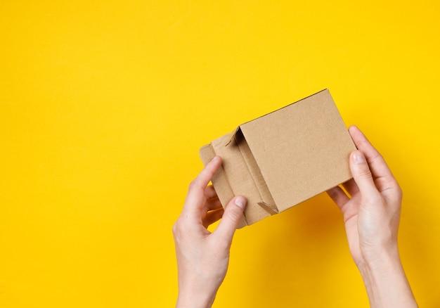 女性の手は黄色の空の段ボール箱を開きます。上面図