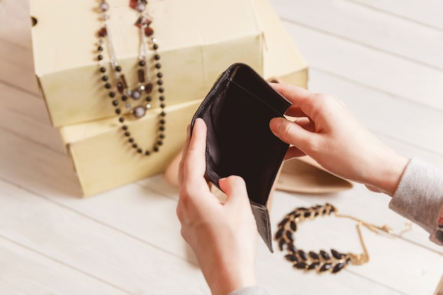Female hands open the empty purse against women clothing and accessories after shopping.