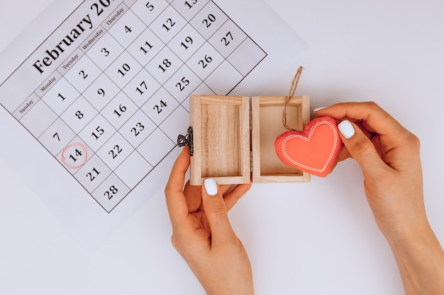 Female hands open a gift with a heart inside on a white background next to a festive calendar with a mark of 14 february.