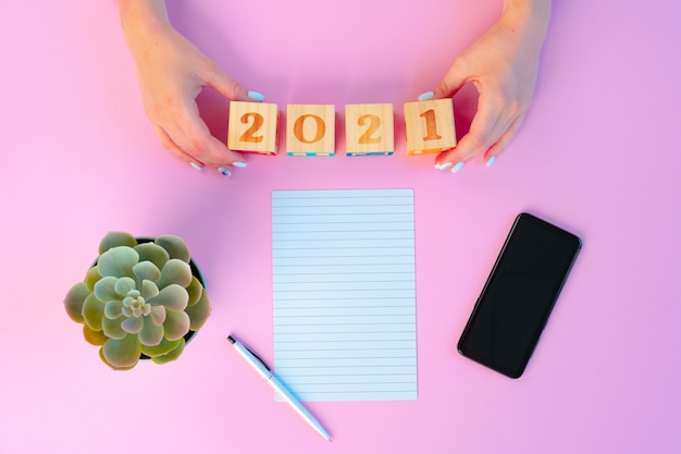 Female hands and open notepad on pink background