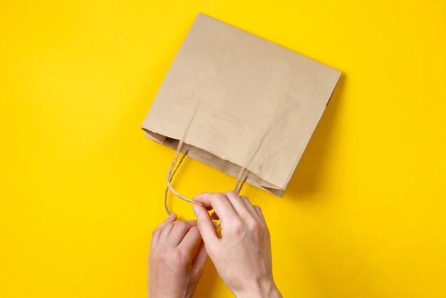 Женские руки открывают бумажный пакет на желтом. вид сверху