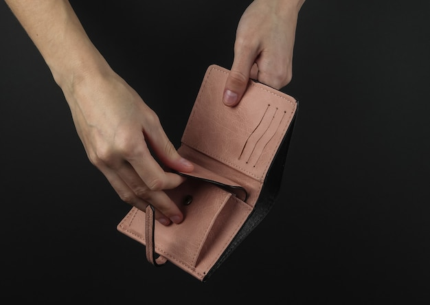 Женские руки открывают розовую кожаную сумочку на черном фоне