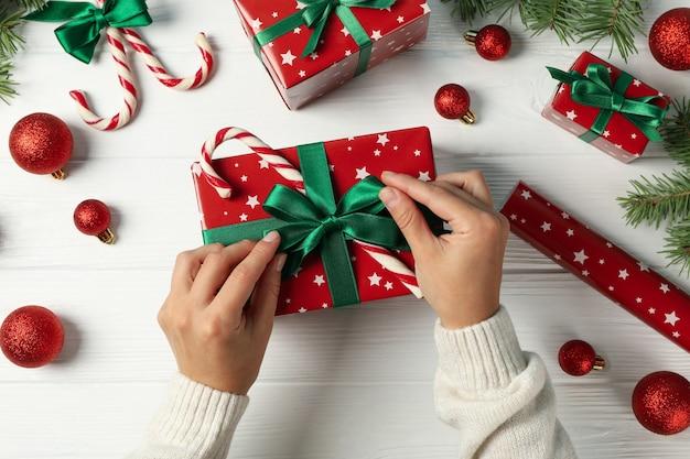 여성 손 크리스마스 액세서리와 함께 흰색 나무 테이블에 상자를 엽니 다