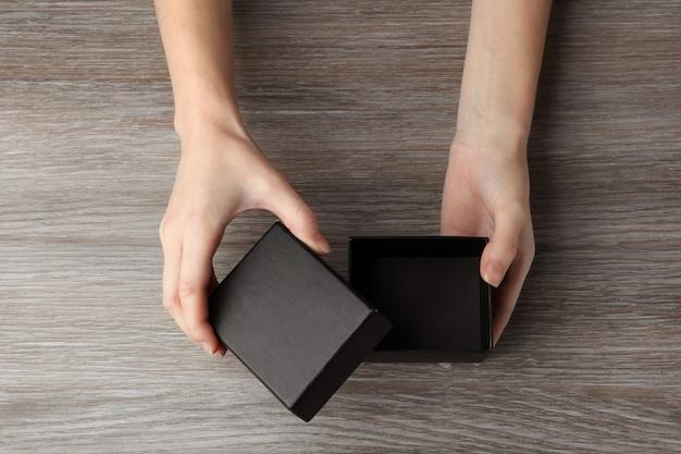 Женские руки открывают черный ящик на деревянных фоне
