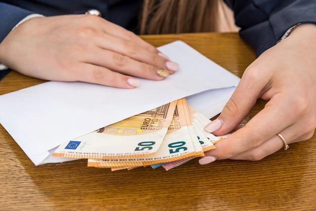 ユーロ紙幣で封筒を開く女性の手
