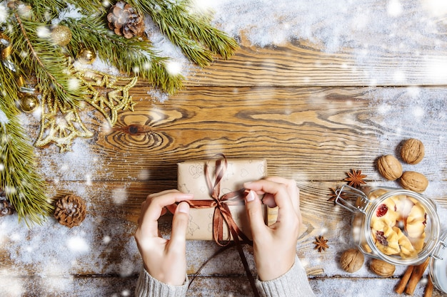 Female hands opening gift box on christmas background
