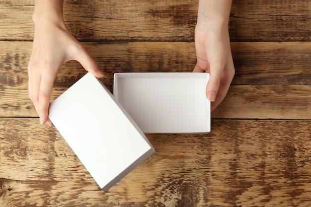 Женские руки открывают белую коробку на деревянном фоне